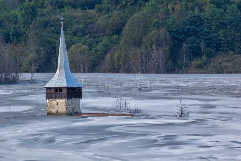 Landschap van een overstroomde kerk in giftig verontreinigd meer toe te schrijven aan kopermijnbouw royalty-vrije stock afbeeldingen