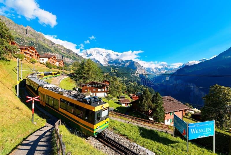 Landschap van een tandradtrein die door de grasrijke helling in Wengen-dorp met sneeuw afgedekte majestueuze Jungfrau-berg reizen royalty-vrije stock foto