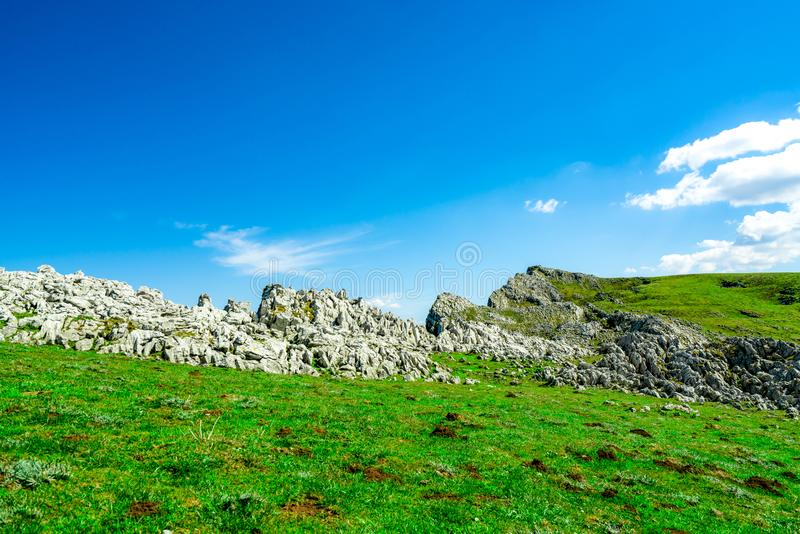 Landschap van groene gras en rotsheuvel in de lente met mooie blauwe hemel en witte wolken Platteland of landelijke mening nave stock foto's