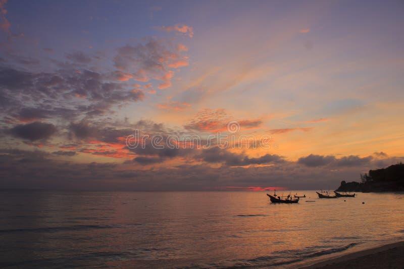Landschap van hemel en overzees dat kleine vissersboot bij dageraad heeft royalty-vrije stock afbeeldingen