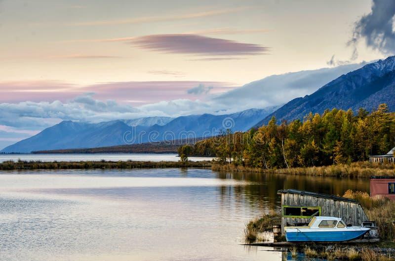 Landschap van het de herfst het bosmeer met berg en boot stock afbeelding