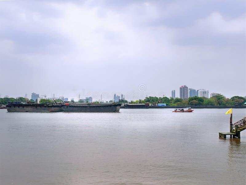 Landschap van Klein Tug Boat Towing Large Barge-Schip in de Rivier stock foto