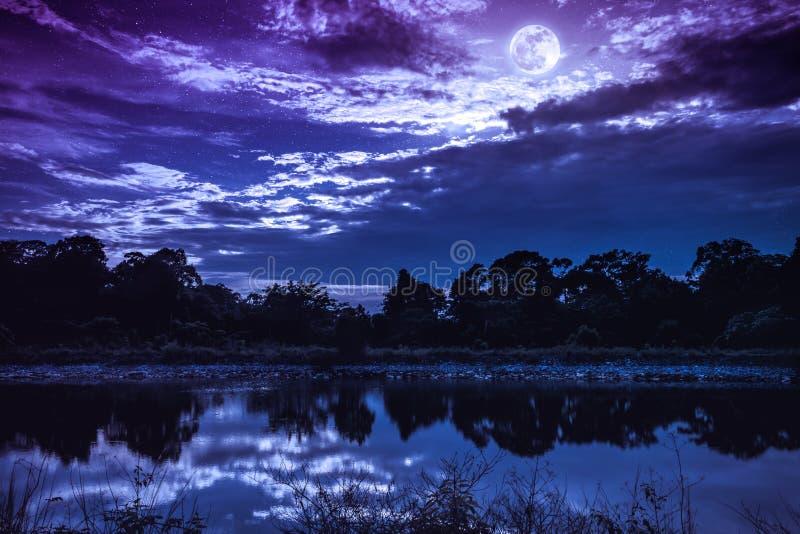 Landschap van kleurrijke hemel met vele sterren en donkere bewolkt Volle maan boven silhouetten van bomen en meer Sereniteitsaard stock foto