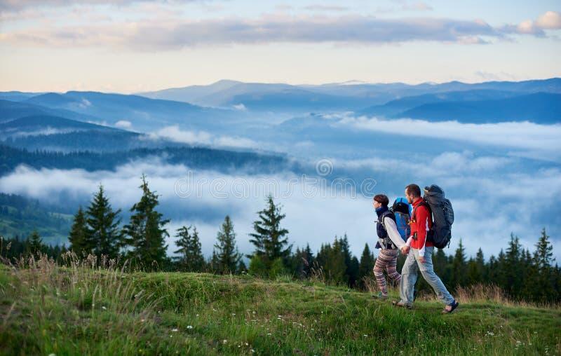 Landschap van machtige bergen met lichte nevel en toeristen die met rugzakken holdingshanden langs bergweg lopen stock afbeeldingen