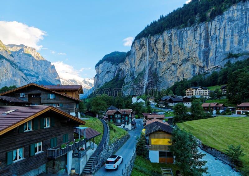 Landschap van mooi Lauterbrunnen-dorp in de ijzige vallei met Staubbach-waterval het hangen onderaan een rotsachtige klip stock afbeelding