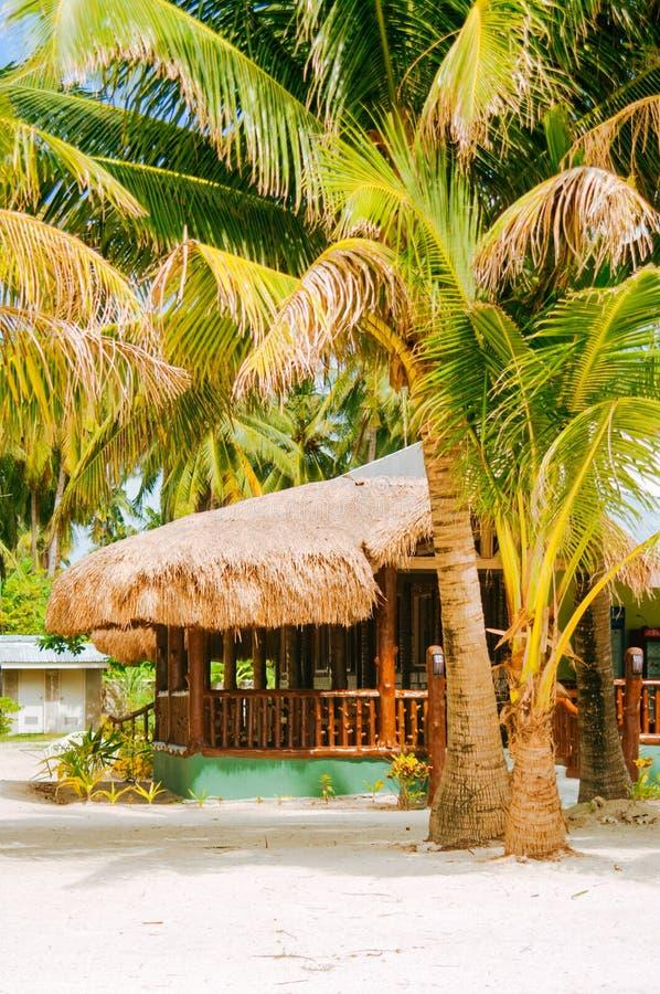 Landschap van paradijs tropisch eiland met palmen, plattelandshuisjes en wit zandstrand in Azië stock foto