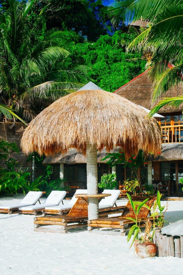 Landschap van paradijs tropisch eiland met palmenplattelandshuisjes en wit zandstrand royalty-vrije stock afbeelding