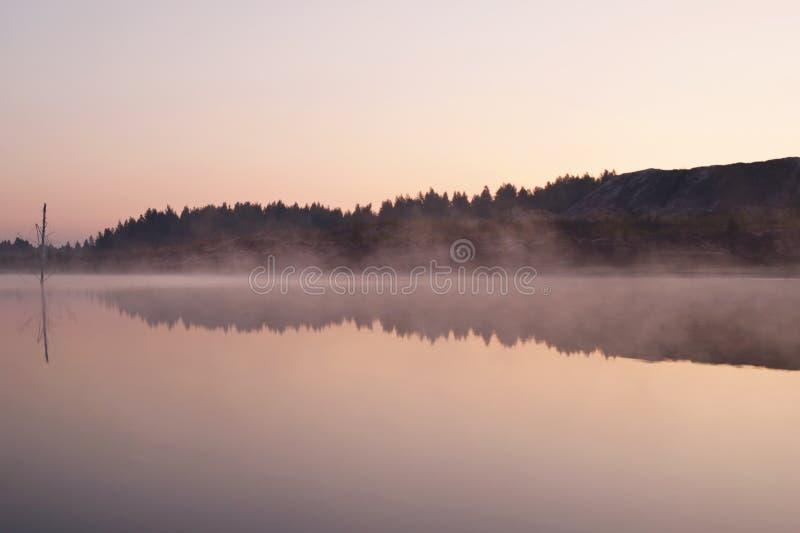 Landschap vroege ochtend op het meer met mist en bezinning van bos en heuvels op een water royalty-vrije stock fotografie