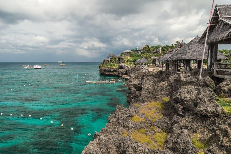 Landschaps azuurblauwe overzees en een rotsachtige kust met het tropische kleine eiland van huizencrystal cove dichtbij Boracay-e royalty-vrije stock foto
