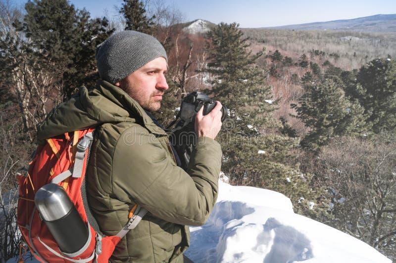 Landschapsfotografie: een mensenwandelaar met een rugzak schiet een landschap in een de winterbos royalty-vrije stock foto's