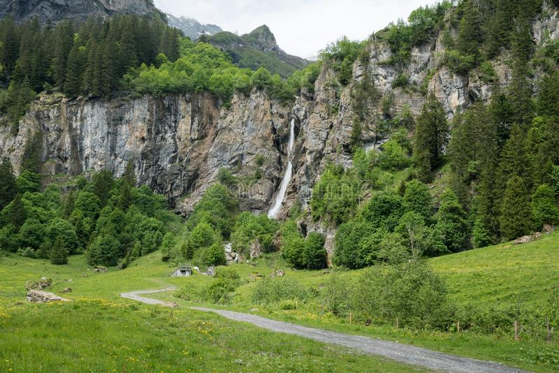 Landschapsmening van een hoge schilderachtige waterval in weelderig groen bos en berglandschap stock afbeeldingen