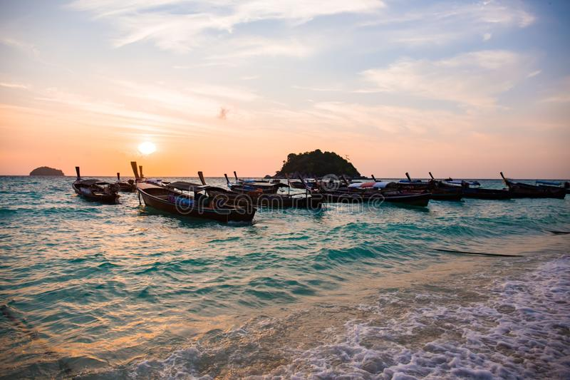 Landschapsmening van zonsondergang op strand met houten boot stock afbeelding