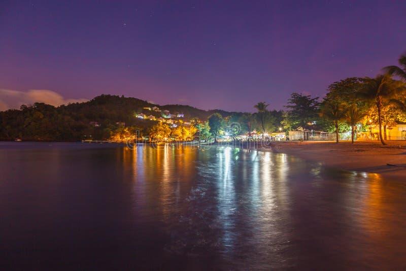 Landschapsweergave van het strand van Anse a l'Ane met palmbomen en kalme baai bij een kleurrijke schemering met een vreedzame Ca stock foto