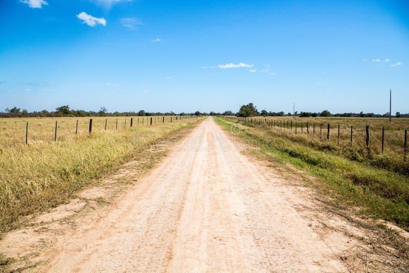 Landschotterweg zwischen Ackerland, nahe Filadelfia, in Deutsch-mennonite Kolonie Fernheim Gran Chaco, Paraguay lizenzfreies stockfoto