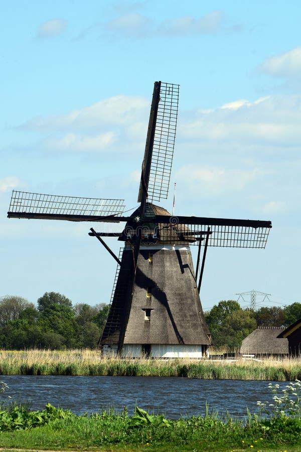Landscpae olandesi con il mulino, il lago e la pista ciclabile immagine stock