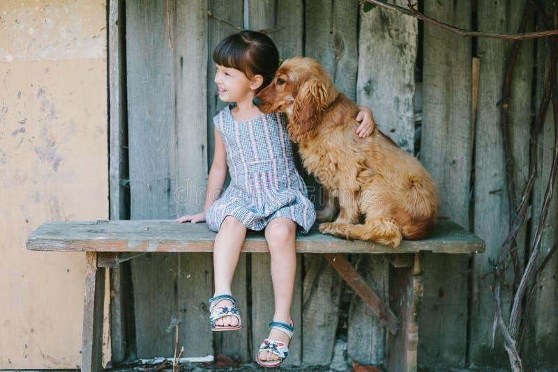 Landsflickasammanträde på en bänk med hennes hund under vinranka Trä royaltyfri fotografi