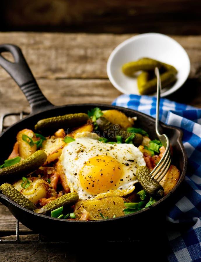 Landsfrukost från potatisar, med bacon och stekte ägg arkivbilder