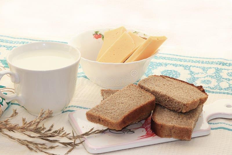 Landsfrukosten, mjölkar och sädes- bröd, skivor av ost, royaltyfri foto