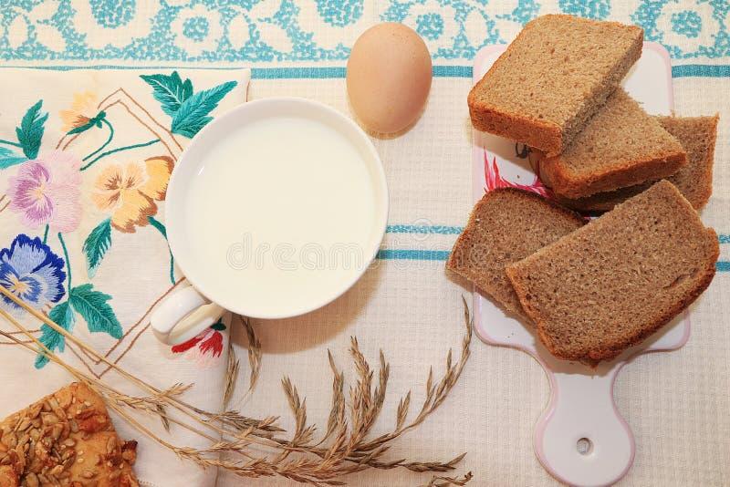 Landsfrukosten, mjölkar och sädes- bröd, skivor av ost royaltyfri bild
