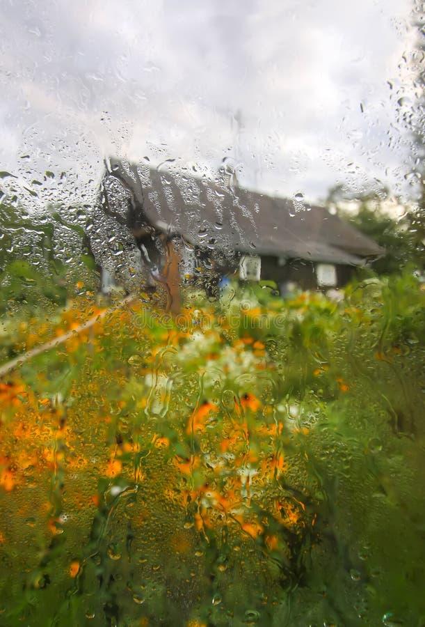 Landsgård med byggnader bak det våta exponeringsglaset med höstregndroppar arkivfoto