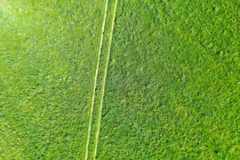 Landsgrusväg bland gröna ängar i sommarfältet, flyg- bästa sikt royaltyfria bilder