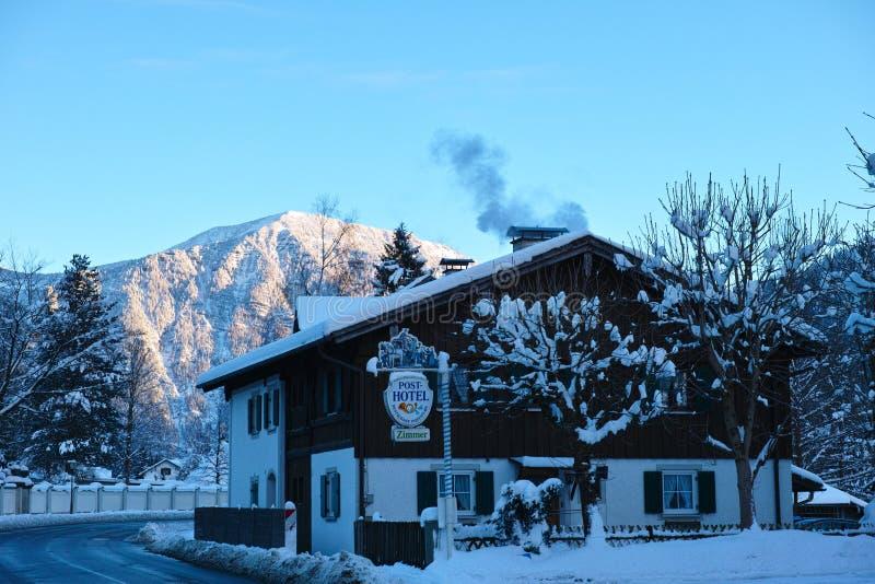 Landshotell i snöig alpint landskap royaltyfri fotografi