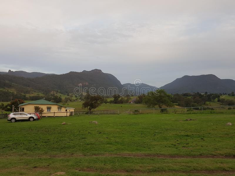 Landshus med bilen, berg och solnedgång arkivbild