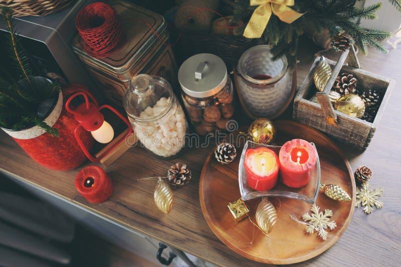 Landshuskök som dekoreras för jul och ferier för nytt år Marhmallows, stearinljus, kakao och muttrar i moderna krus arkivfoton