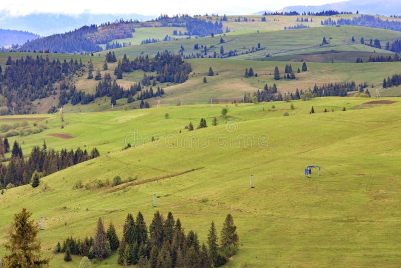 Landskap av de Carpathian bergen för vår med blåa master av en bergkabelelevator som leder till överkanten av berget royaltyfri fotografi