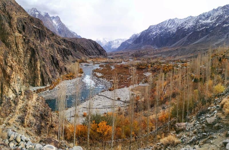 Landskap av den blåa turkosfloden som passerar till och med färgrik höst i korkade berg för dal som och för snö är pakistanska i  royaltyfria foton