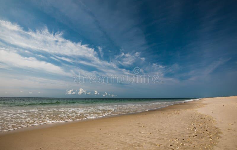 Landskap av den tomma stranden på en Sunny Day med ljus blå himmel för försiktiga vågor med vita moln royaltyfri bild