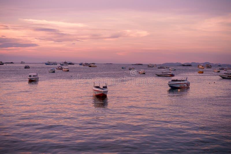 Landskap av den tropiska stranden med den gamla fiskeb?ten som parkeras p? stranden i skymningsolnedg?ng i Pattaya, Thailand Land royaltyfri foto