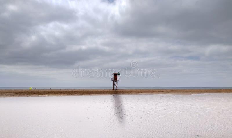 landskap av en strand med molnig himmel och en högväxt livräddarestation med den gröna flaggan på mitt Först har havsvattnet royaltyfri foto