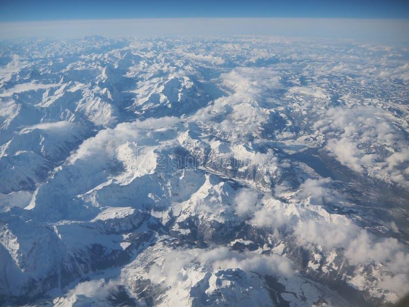 Landskap av fjällängarna under vinter med ny snö Beskåda från flygplan arkivfoton