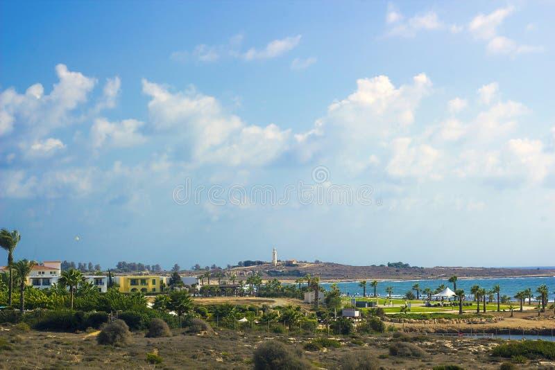 Landskap av Paphos med hus, träd och fyren, Cypern royaltyfria bilder