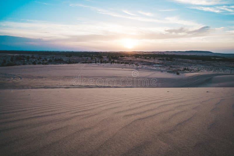 Landskap av solen över horisont i öken på vita sanddyn Mui Ne, Vietnam Bygdpanorama under scenisk färgrik himmel på arkivbilder