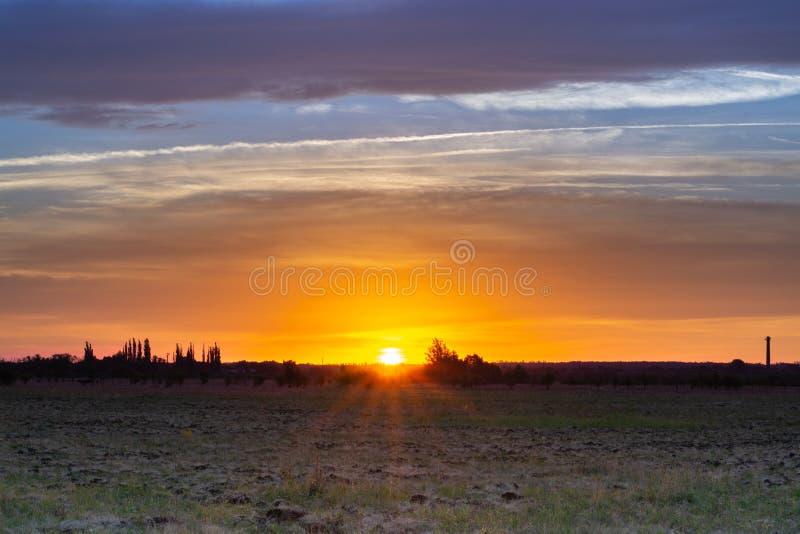 Landskap av soluppgång i ett fält utanför arkivbild