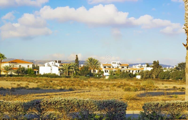 Landskap av staden Paphos med hus, träd och berg arkivfoto