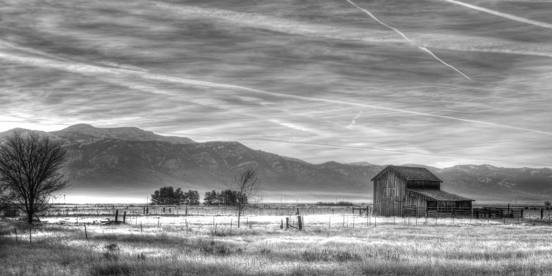 Landskap bilden av en gammal ladugård på en ranch med moln och berg royaltyfria bilder