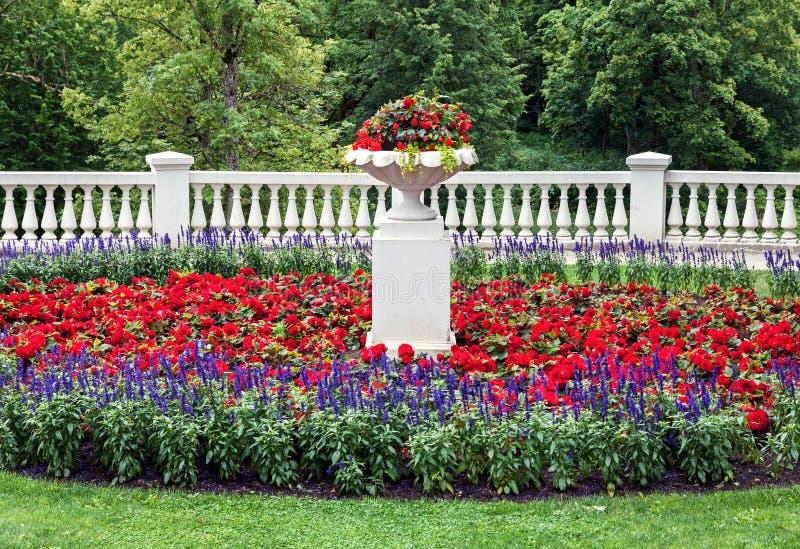 Landskap blomsterrabatt med klassiska arkitekturdetaljer arkivfoto