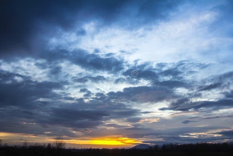 Landskap den dramatiska solnedgången och soluppgånghimmel med en kontur av t arkivfoto