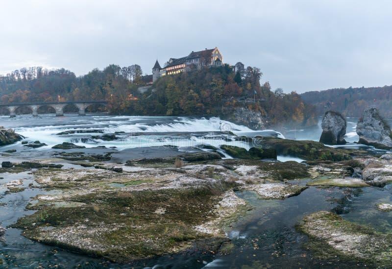 Landskap för aftonljuspanorama av den Rhine Falls och Laufen slotten i Schweiz med mycket lågvattennivån i sen höst royaltyfri fotografi