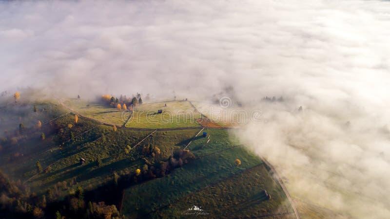 Landskap för Bucovina höstsoluppgång i Rumänien med mist och berg royaltyfri bild