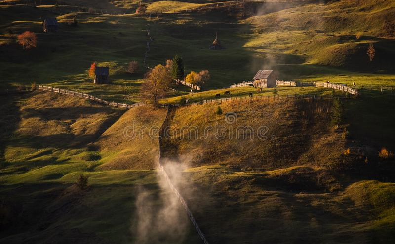 Landskap för Bucovina höstsoluppgång i Rumänien med mist och berg arkivfoto