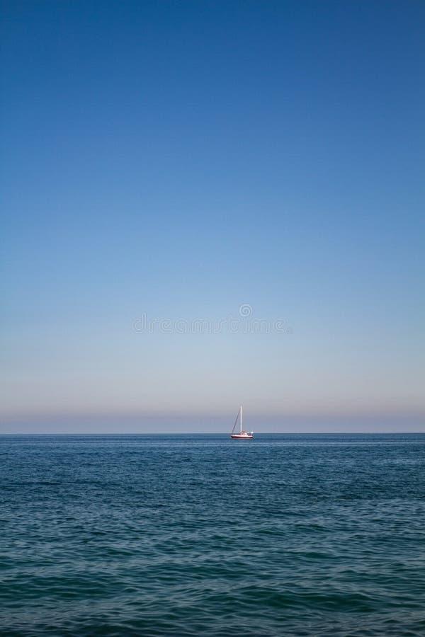Landskap för havsvatten med mörkervågor och en ensam röd yacht för vit och på horisonten på solig dag fotografering för bildbyråer