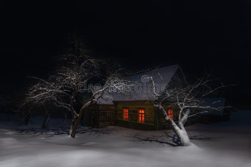 Landskap för nattvinterjul med det gamla Snö-täckte sagahuset bland snödrivorna och träden Sceniska forntida ryska Ol arkivbild