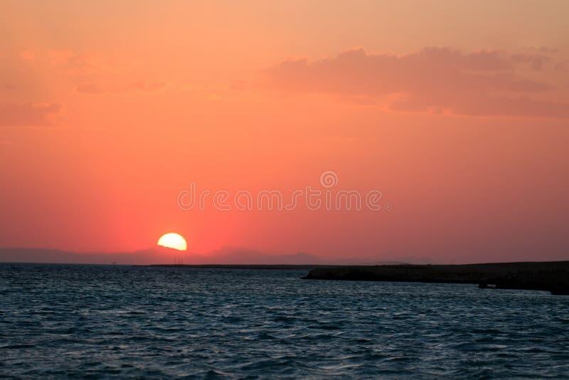 Landskap för orange och röda färger för solnedgång, hav och sol med djup himmelbakgrund Obebodda öar av Röda havet, Egypten, Afri arkivfoto