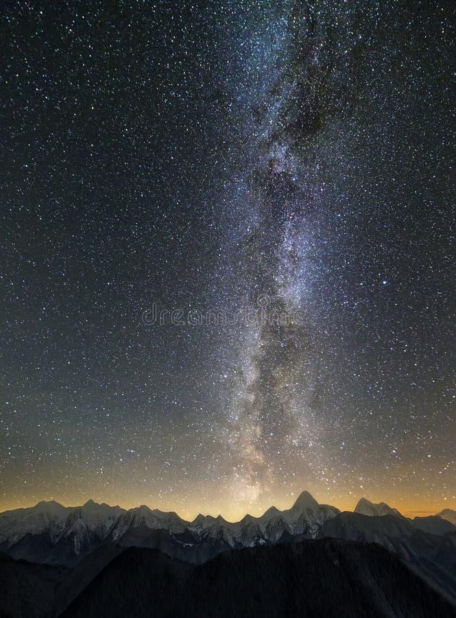 Landskap för panorama för bergvinternatt Branta bergmaxima som täckas med snö och den prydliga skogen som tänds av horisonten för arkivbilder
