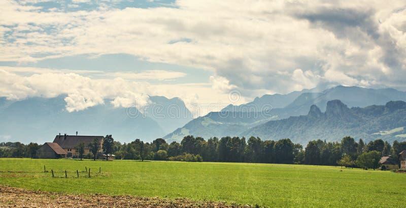 Landskap för sommarbergbygd med ett fält, en skog och byggnader Harmoni av naturen och ekonomisk aktivitet royaltyfria foton