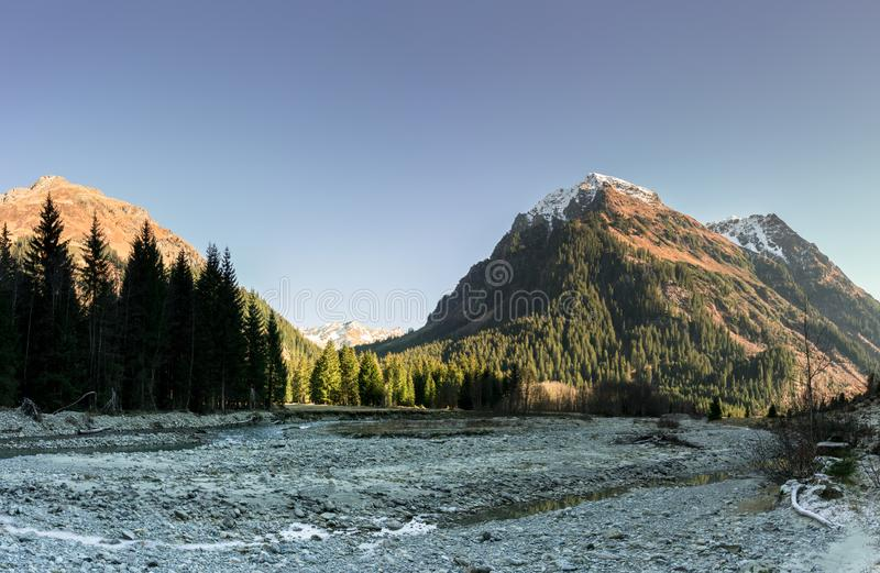 Landskap för stenigt berg i tidig vinter med snö-korkade maxima och färgrik skog och en bergström i förgrunden med I arkivfoto